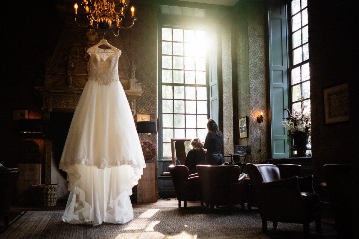 Voorbereidingen van de bruid en de jurk hangt prachtig in het kasteel mooi licht