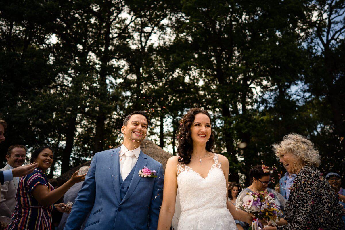 Blij bruidspaar loopt na de ceremonie weg