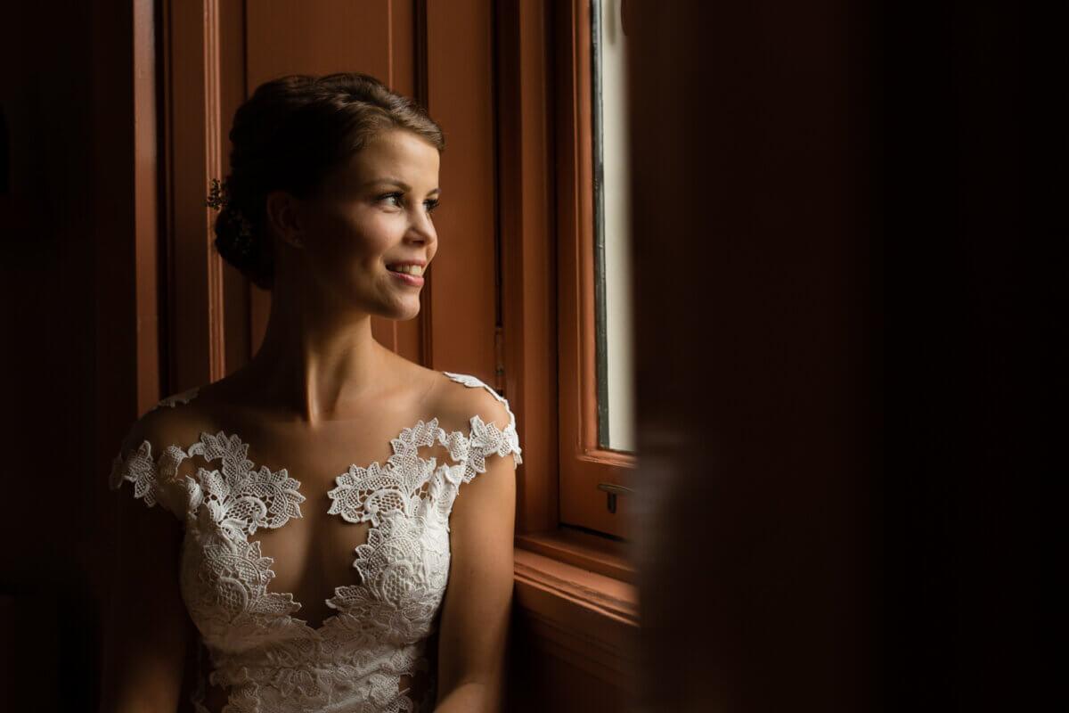 Bruid met prachtige jurk in het licht van het raam als de schilder vermeer