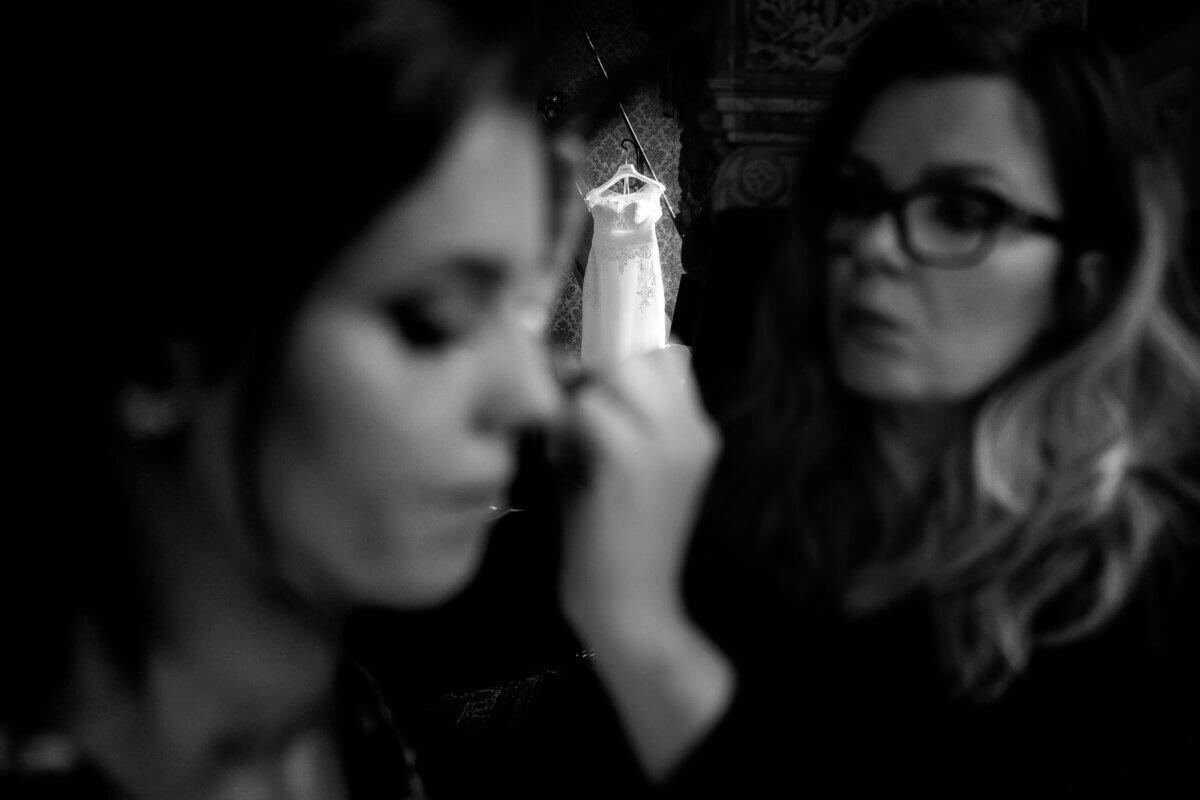 Bruid in de make-up met jurk in het licht hangen