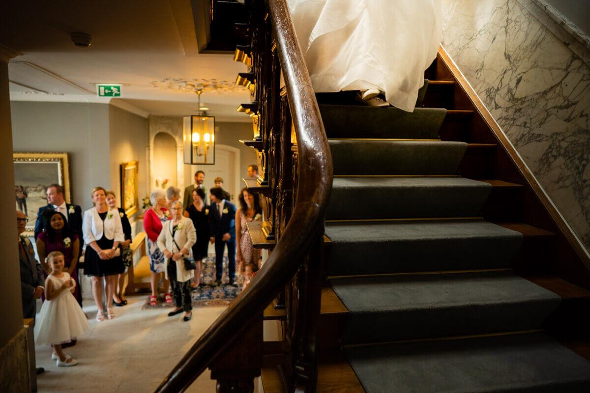 Bruid komt van de trap af lopen en alle gasten staan klaar