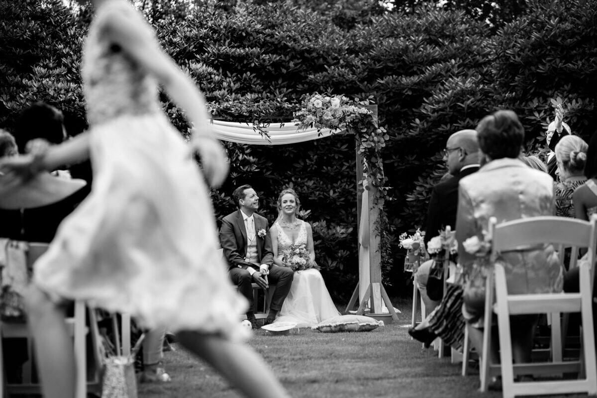 Bruidsmeisje rent voor bruidspaar langs