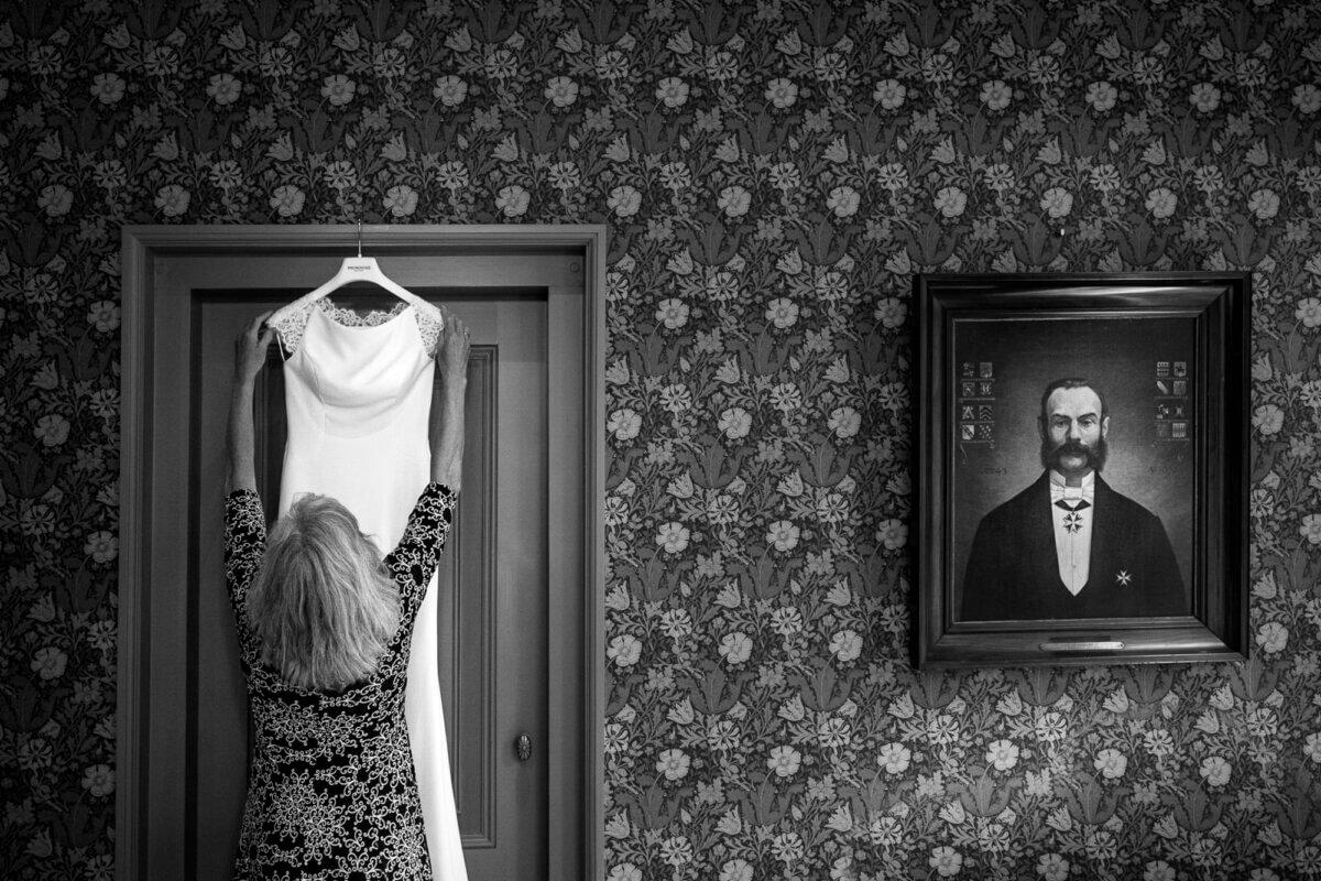 Foto van moeder van de bruid die jurk ophangt
