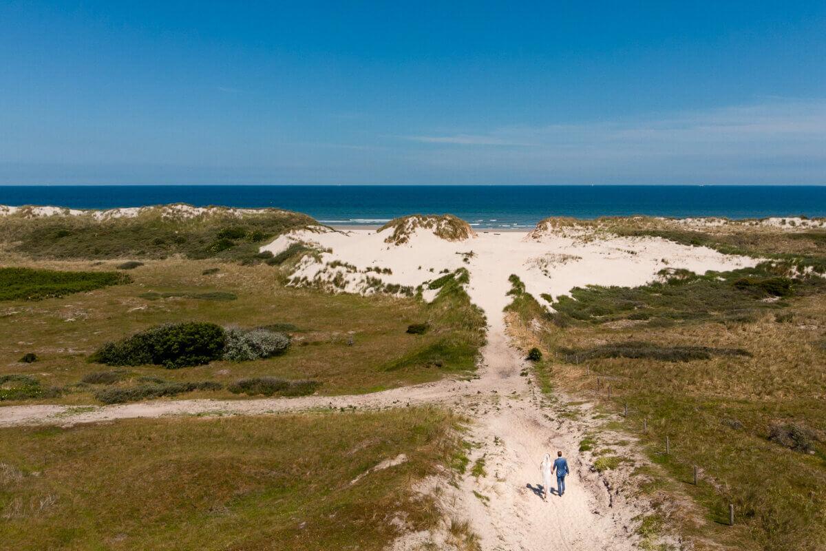 Bruidpaar loopt door duinen van Ameland met drone
